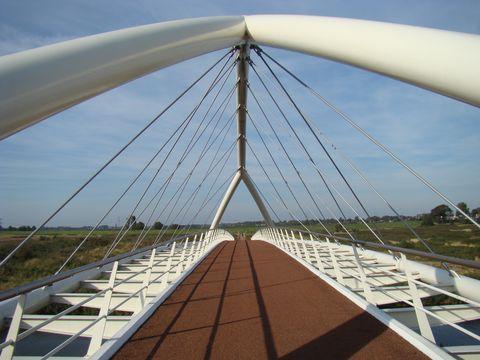 z cyklostezky v pastvinách odbočí cyklisté na moderní most, pro auta je jiný