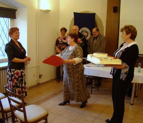 M. Vincencová předává Míle Bradové grafický list a Věra Veselá vlastnoručně vytvořený dort