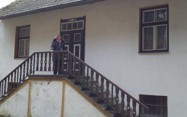 paní Lidmila Anna Dohnalová přede dveřmi bytu, kde strávila prvních dvacet let života (levé okno je z Vodičkovy kuchyně); foto Silva Poukarová