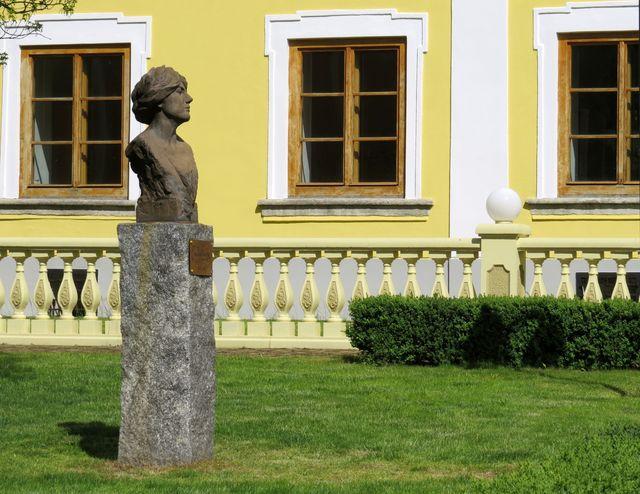 busta Emy Destinnové v zahradě před vchodem do zámku