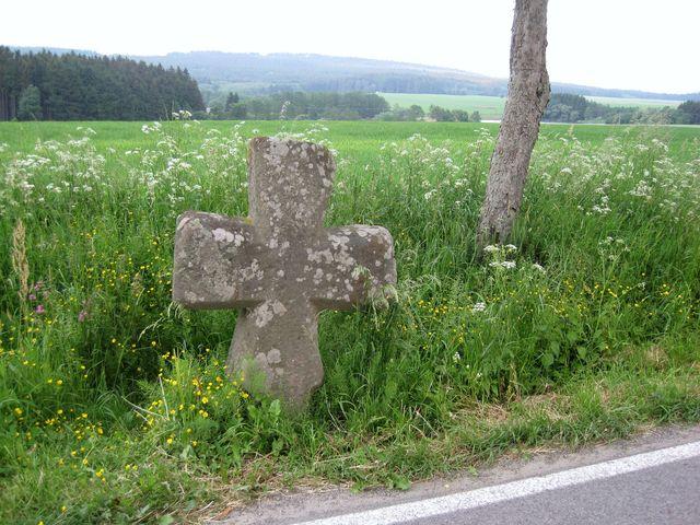 kamenný kříž Baba chrání tajemství svého původu