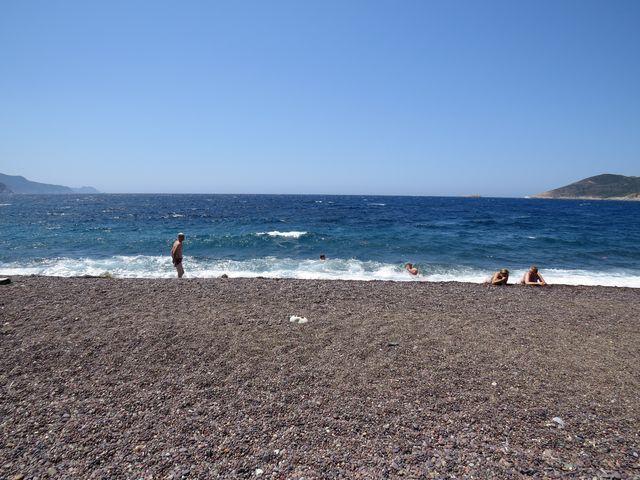 rozpálená oblázková pláž a obrovské vlny