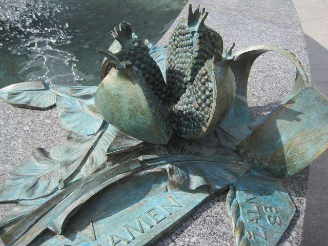 v rozích trojúhelníkové kašny jsou atributy sv. Zdislavy - zde rozčtvrcené granátové jablko