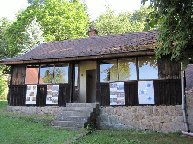 na stěně malé chaty z roku 1913 je výstava z činnosti odboru KČT Čeřínek