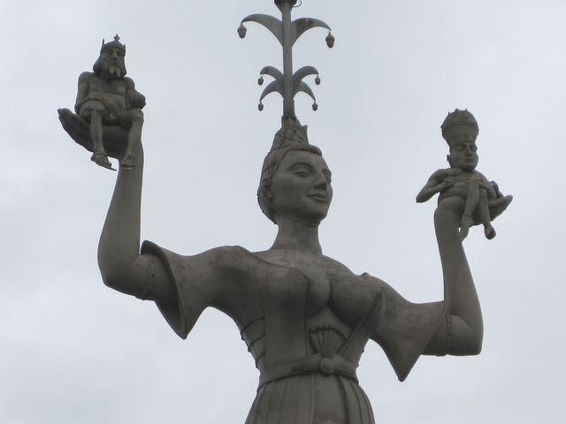 kurtizána drží v levé ruce postavičku císaře Zikmunda, v pravé papeže Martina V.