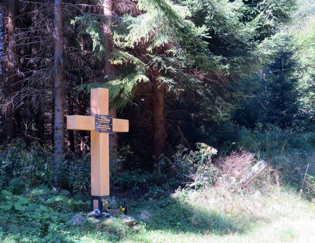na desce připevněné ke kříži je nápis: In memoriam. Na památku bývalé obce Fláje.