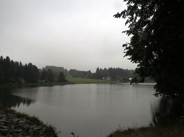 zachmuřený rybník Kachlička a travnatá pláž v létě vyhledávaná mnoha rekreanty