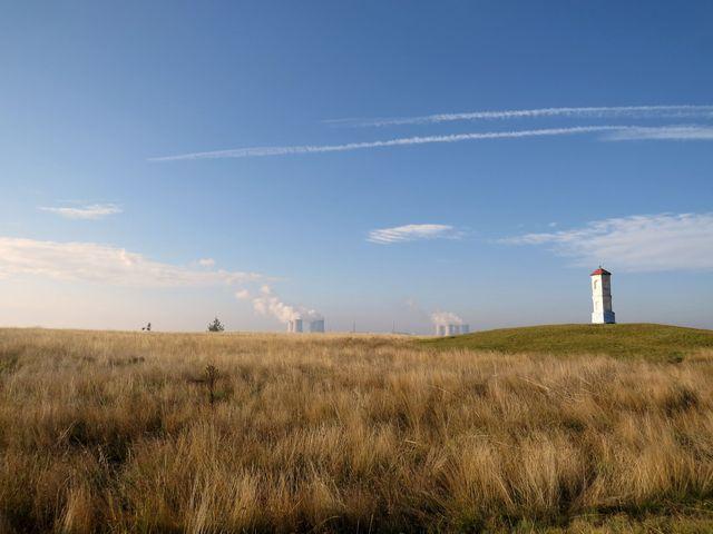 na jedné z mohyl na okraji stepi stojí boží muka, na obzoru chladicí věže se sloupci páry