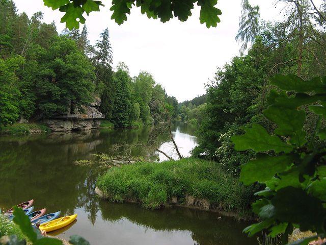 soutok Židovy strouhy s Lužnicí - nad hladinou řeky je vidět visutá lávka a nad ní skalní převisy; foto J. Daňhel